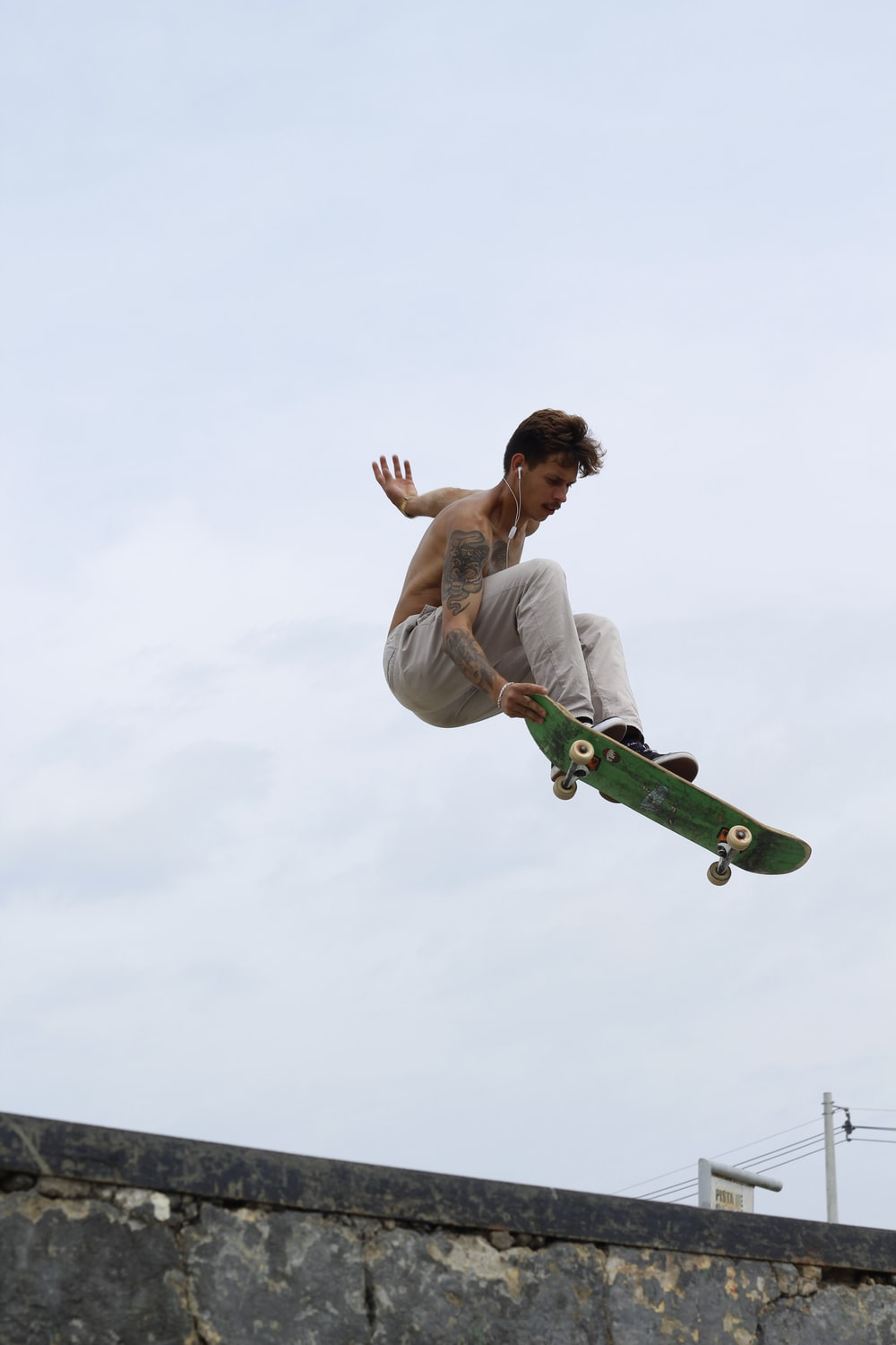 man in white tank top and green pants riding green skateboard during daytime