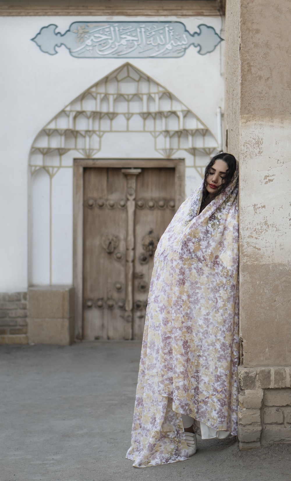 woman in white and pink floral hijab standing near gray concrete wall during daytime