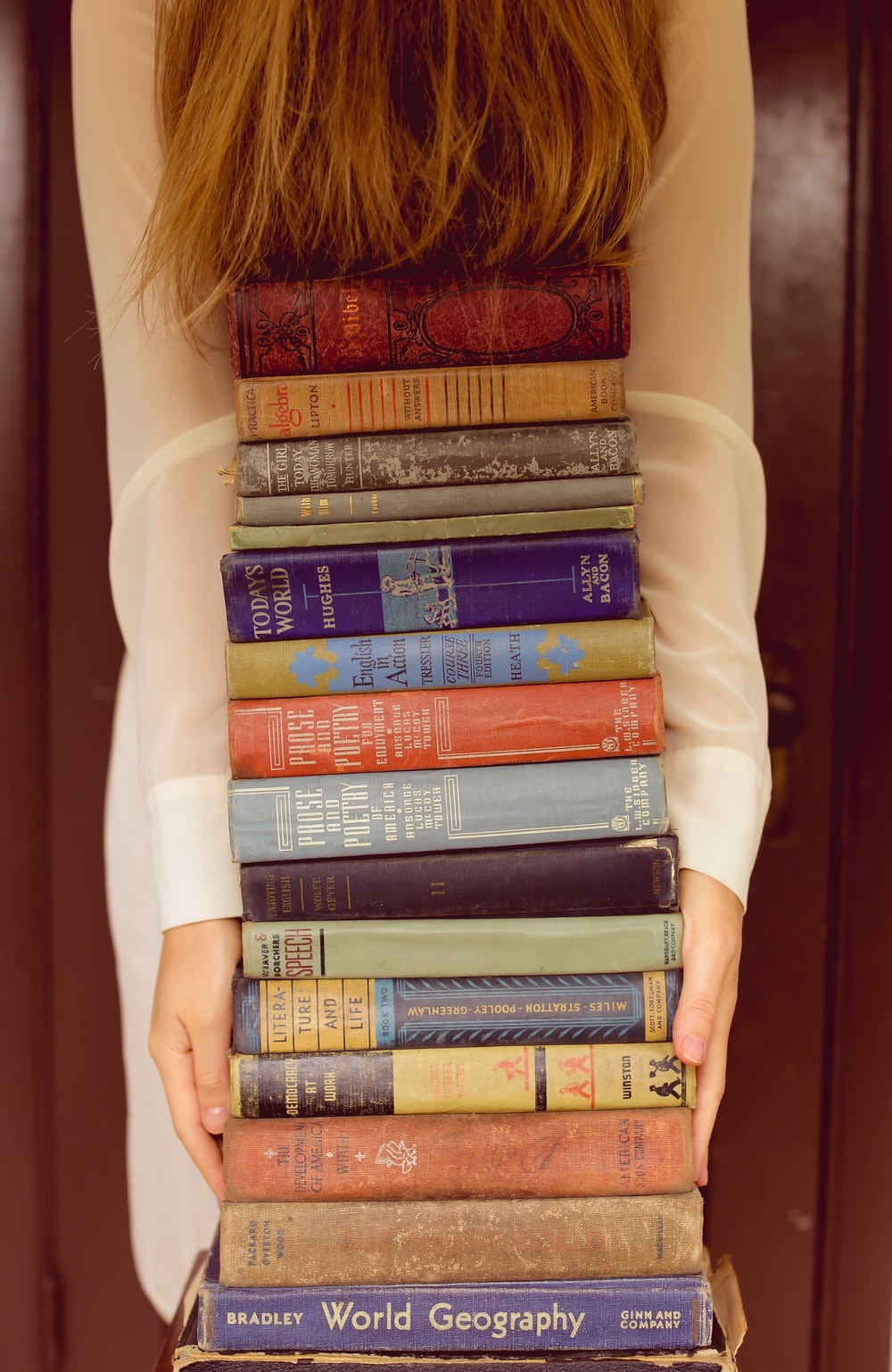 woman in white long sleeve shirt standing beside books