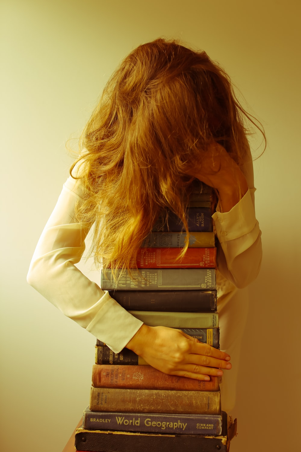 woman in white long sleeve shirt holding book