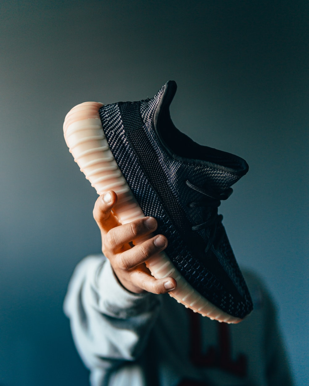 person holding black nike athletic shoe