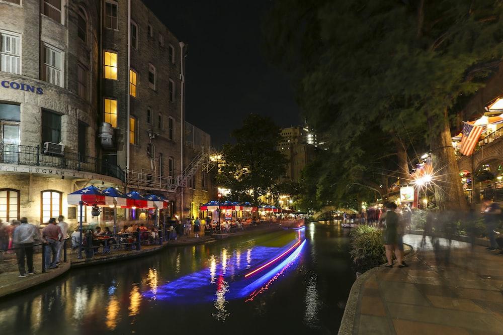 people walking on sidewalk near river during night time