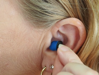 woman wearing blue stud earring