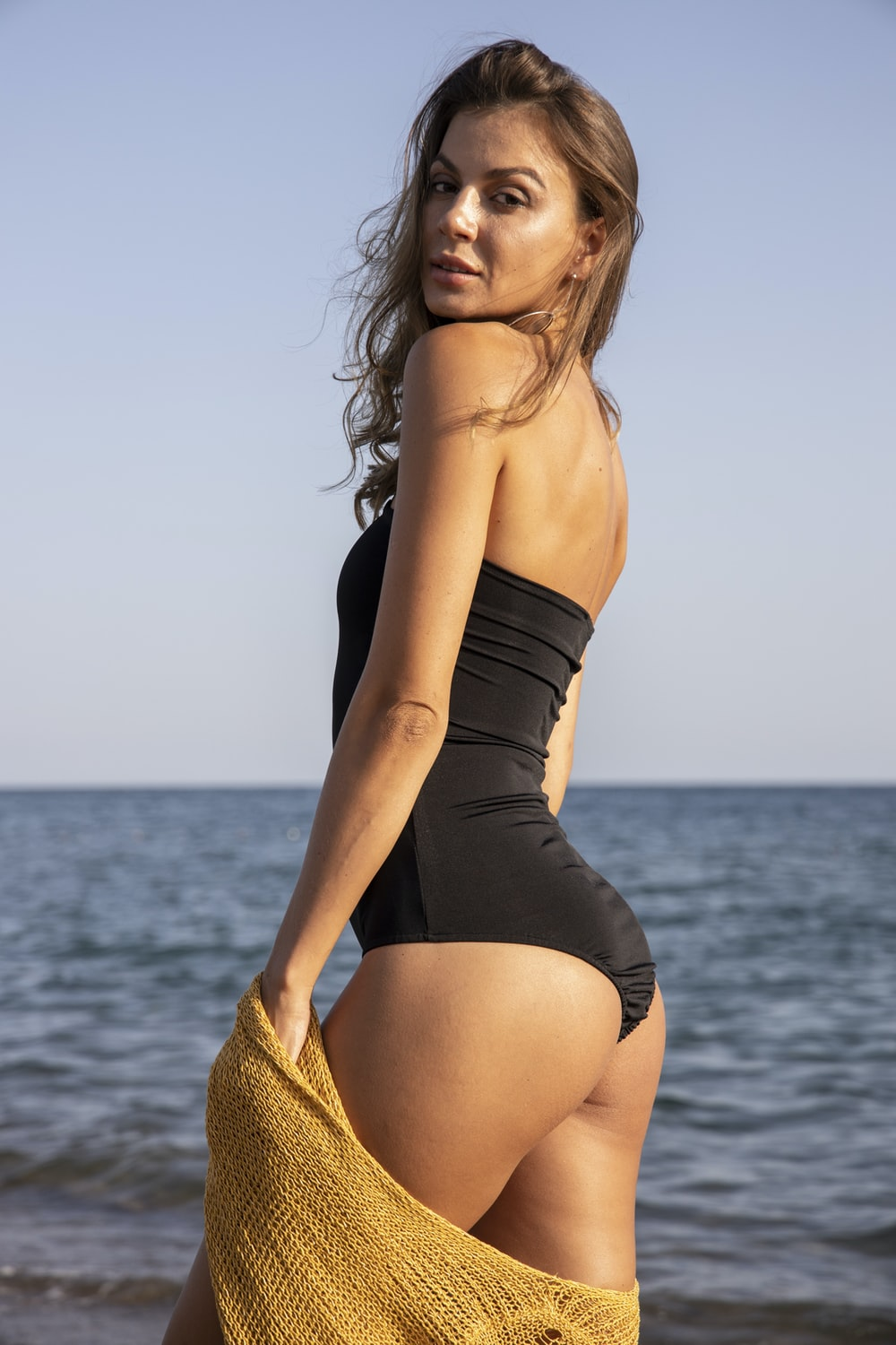 woman in black one piece swimsuit standing on sea shore during daytime