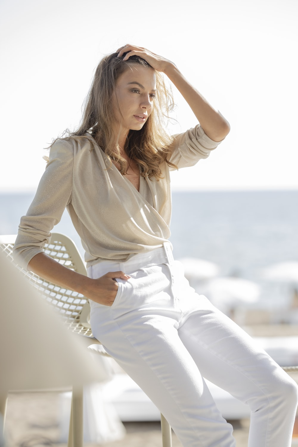 woman in white long sleeve shirt and white pants sitting on white concrete wall during daytime