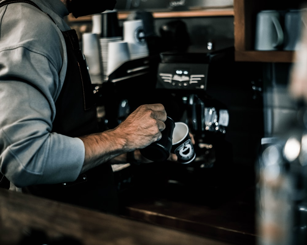 person in gray jacket holding black and silver coffee maker