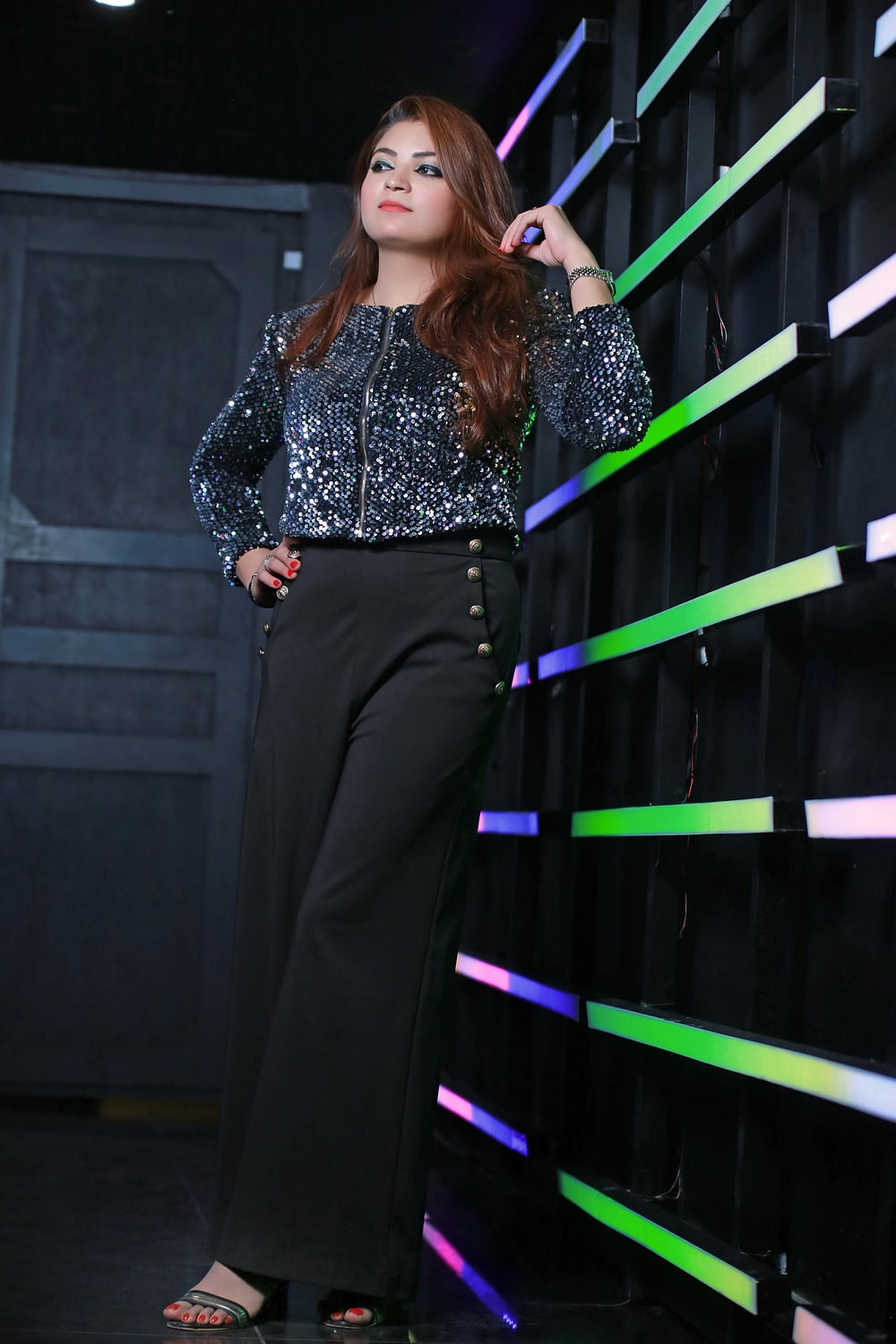 woman in black and white long sleeve shirt and black pants standing on black staircase