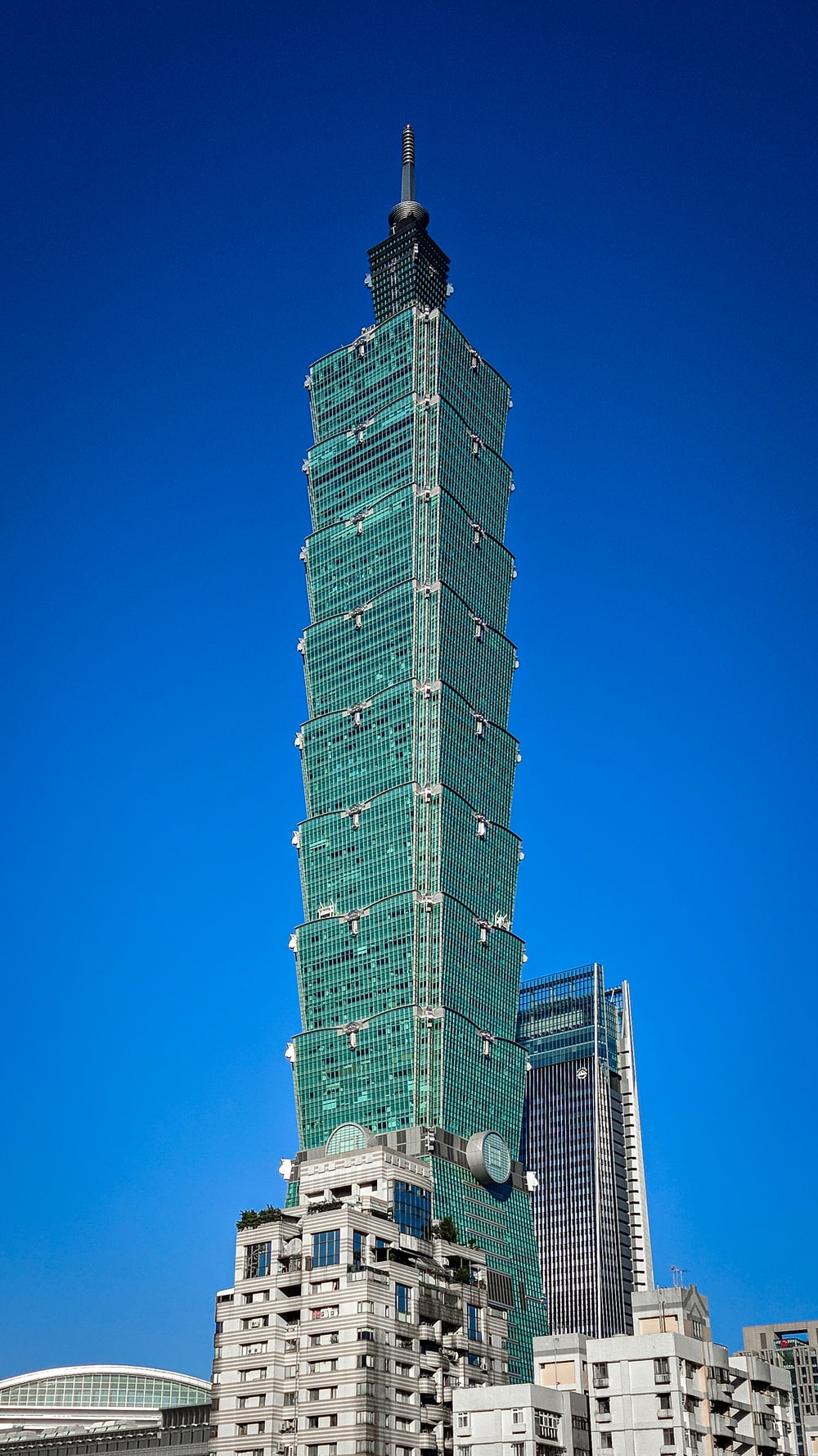 green and white high rise building under blue sky during daytime