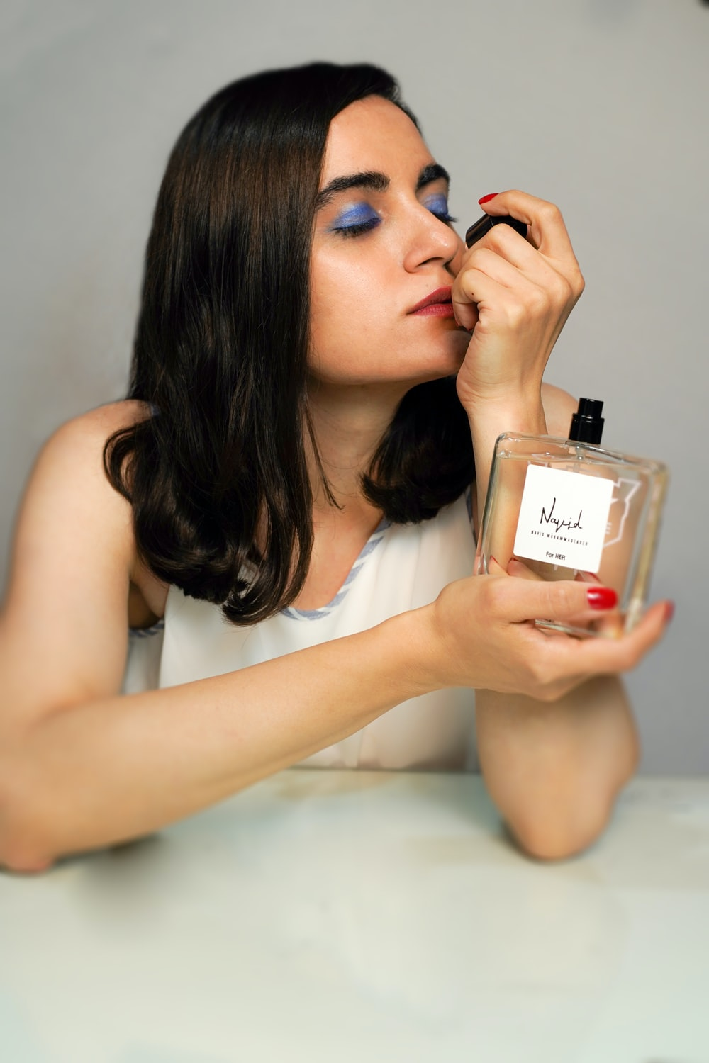 woman in white tank top holding perfume bottle