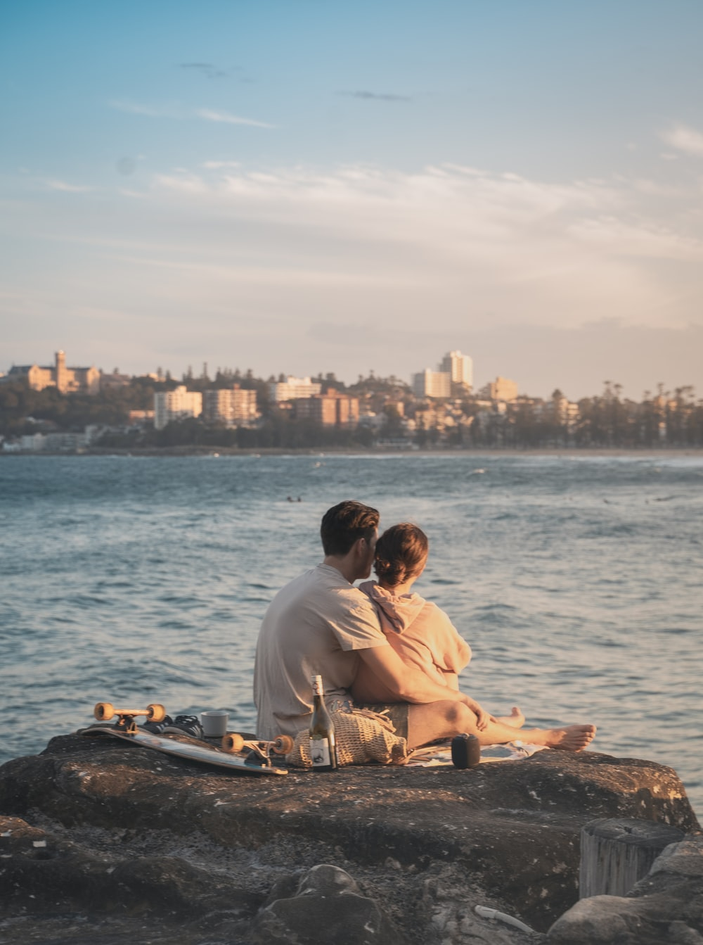 man and woman sitting on rock near sea during daytime