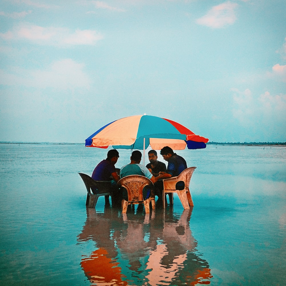 people sitting on beach chairs under blue sky during daytime