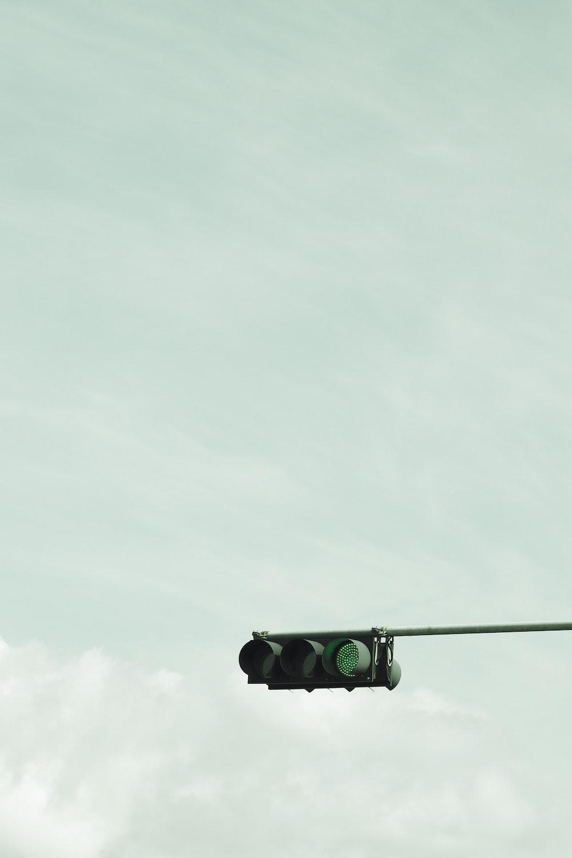 green and black traffic light under white sky during daytime
