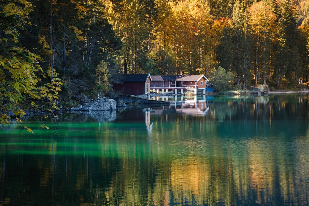 brown wooden house on lake during daytime