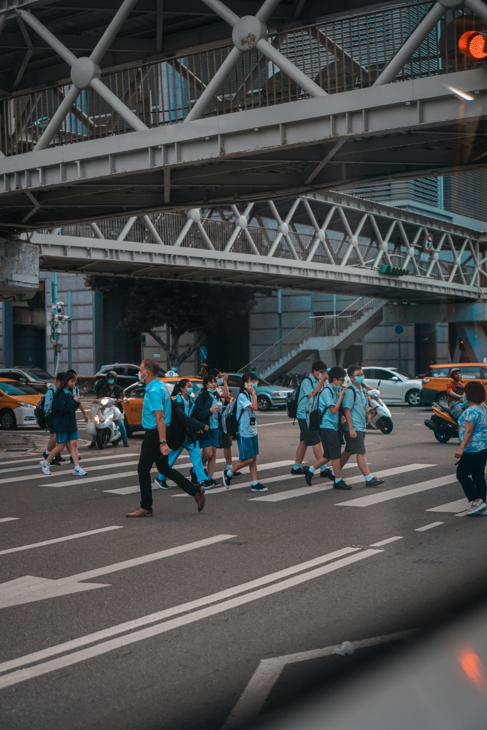 people in blue and orange shirts running on road during daytime