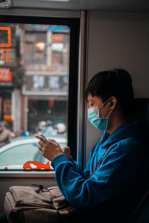 woman in blue hoodie using smartphone