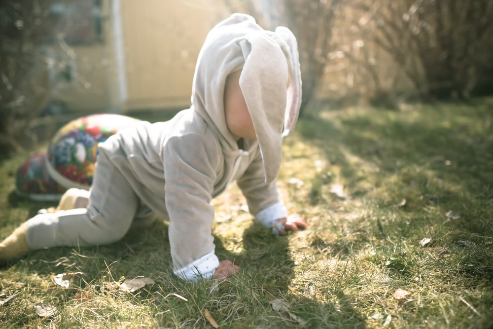 child in white hoodie and pants sitting on green grass during daytime