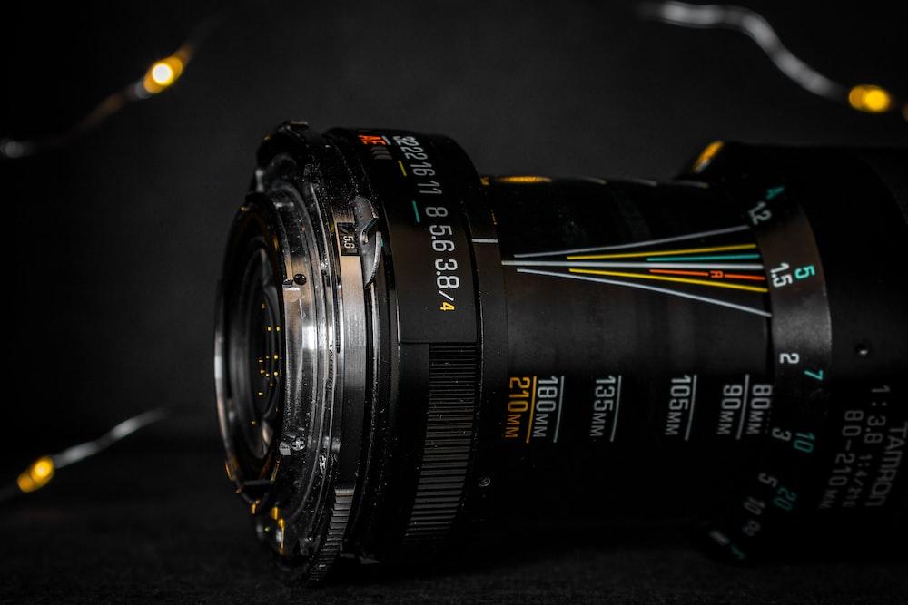 black nikon camera lens on black surface