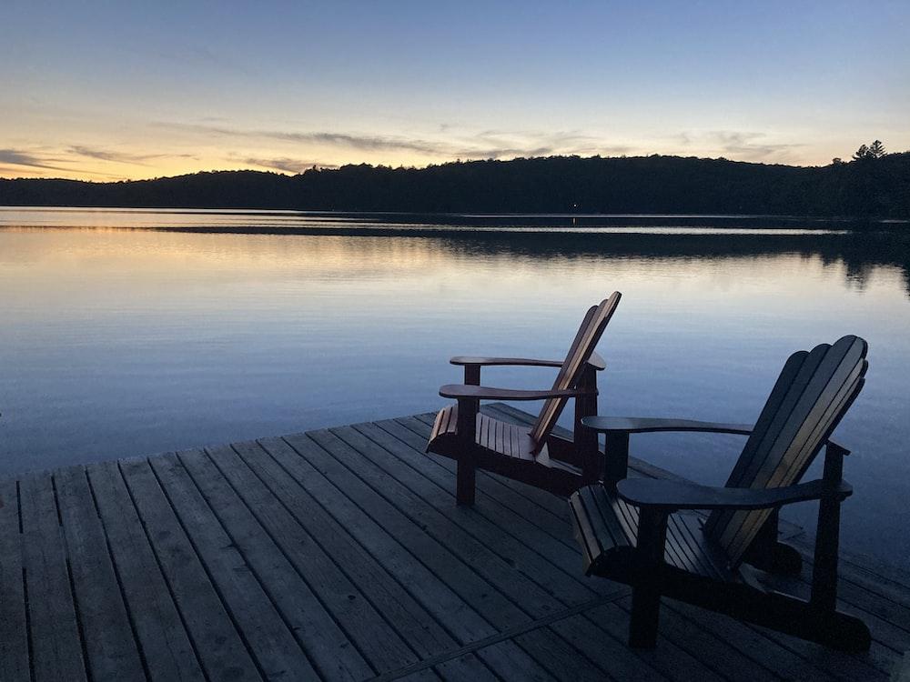 brown wooden bench on dock near lake during daytime