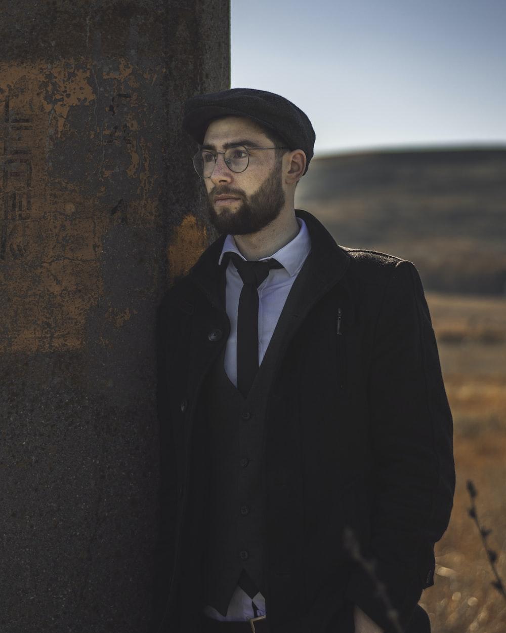 man in black suit jacket standing beside brown wall