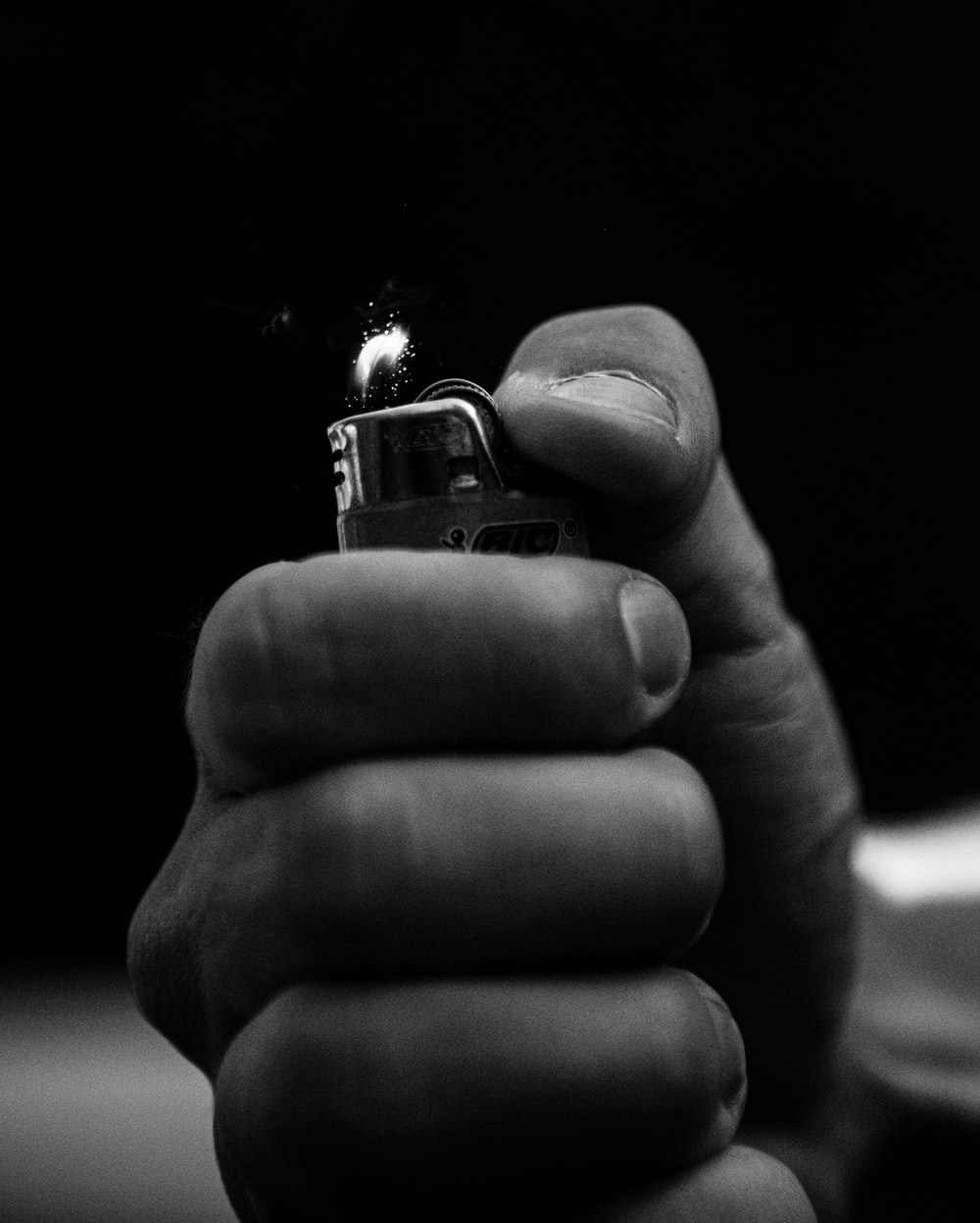 grayscale photo of person holding lighter