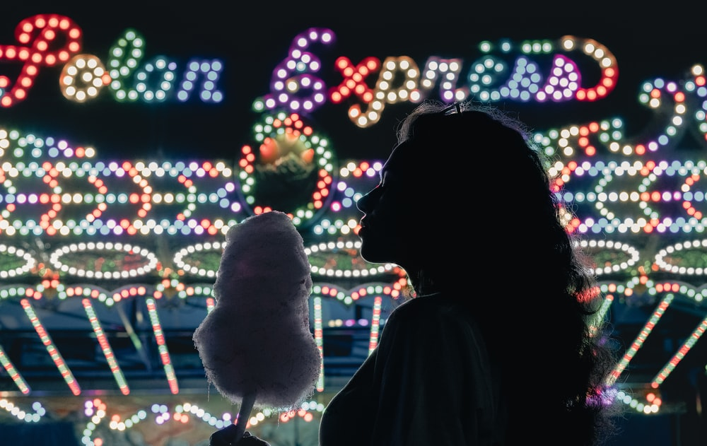 silhouette of woman standing near lighted christmas tree during night time