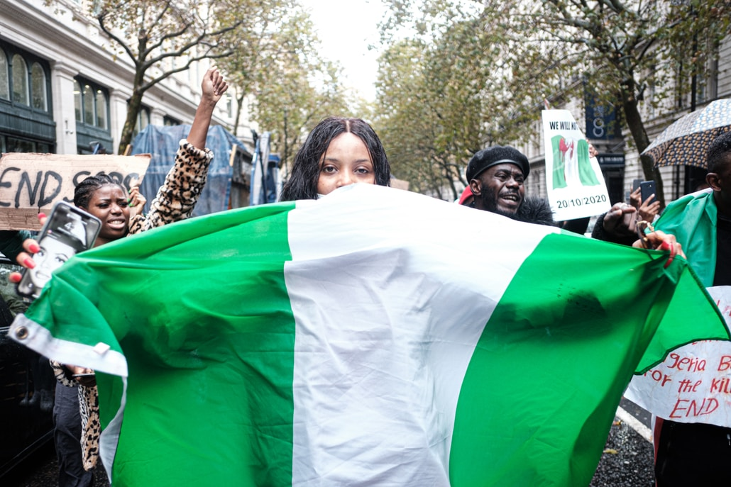 woman in black and white shirt holding white and green flag during daytime