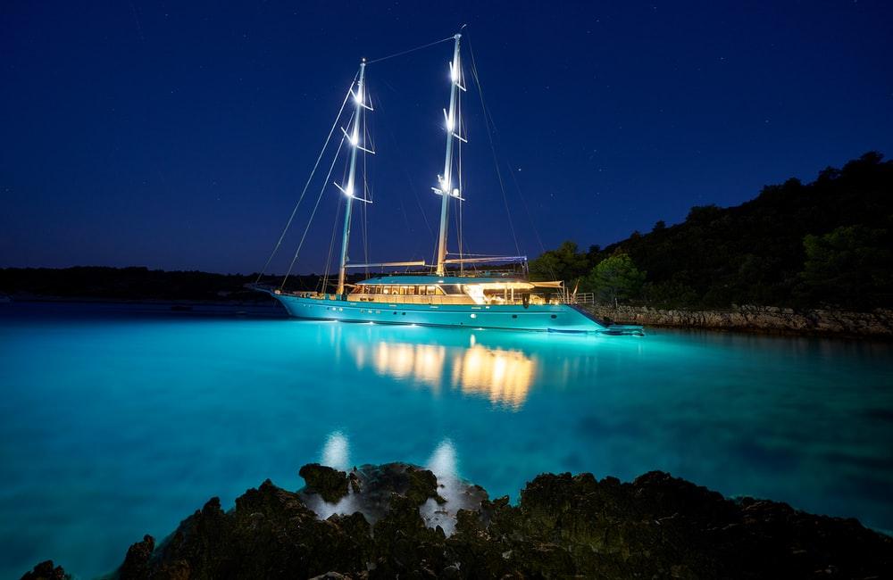 brown and white sail boat on blue body of water during night time
