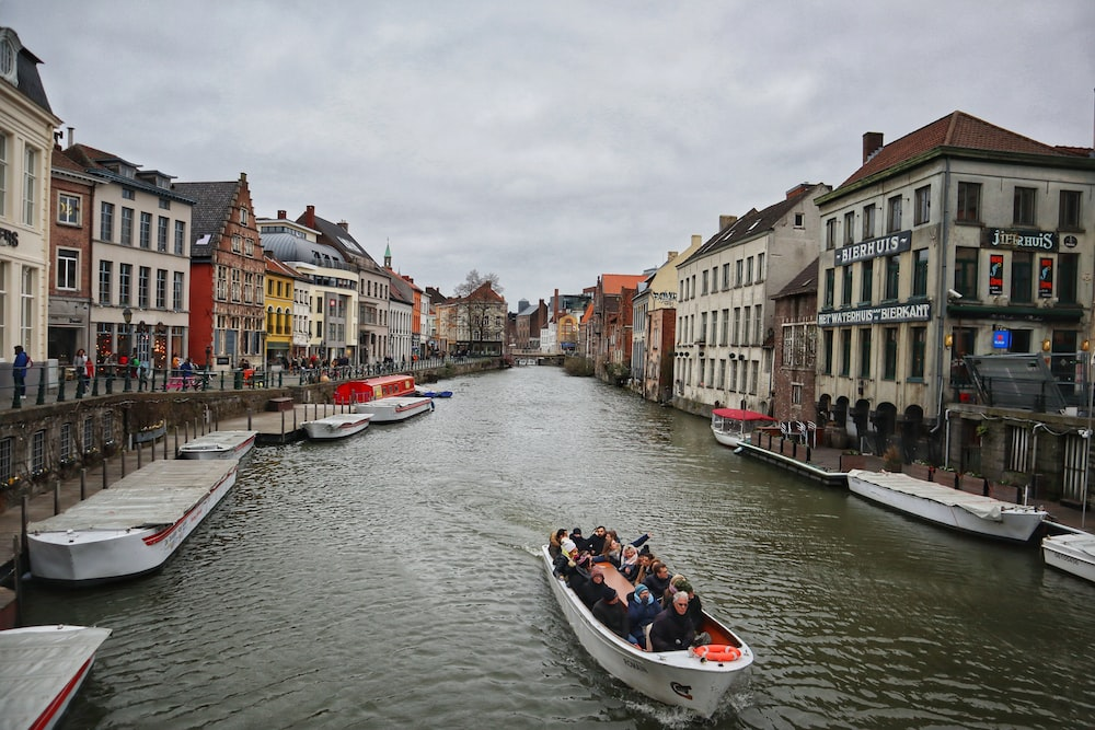 people riding on boat on river between buildings during daytime