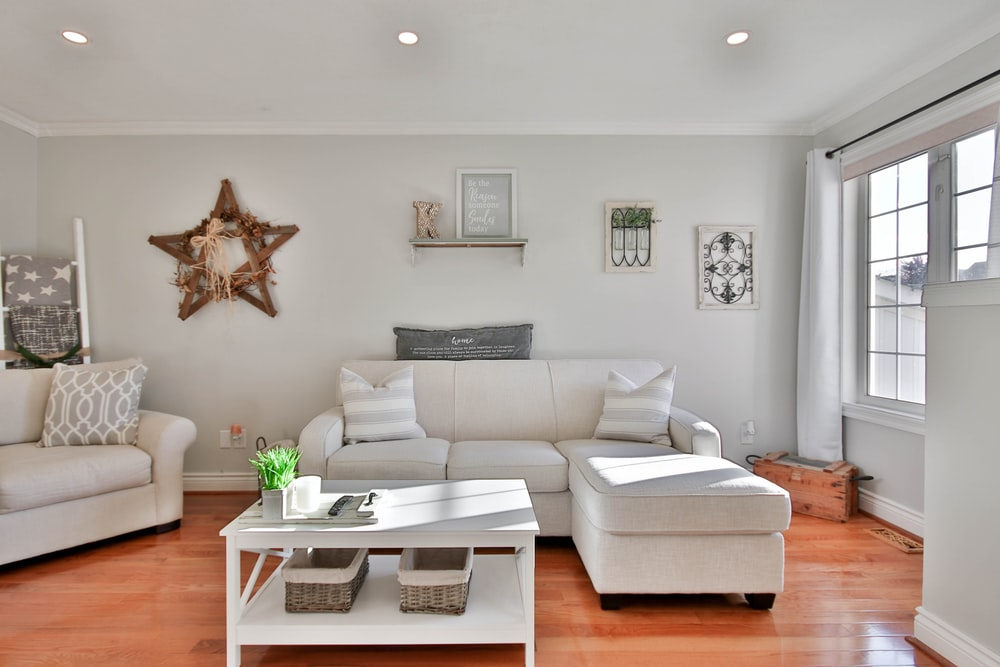 white leather sofa beside brown wooden table