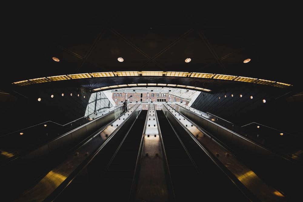 white and black escalator in a tunnel