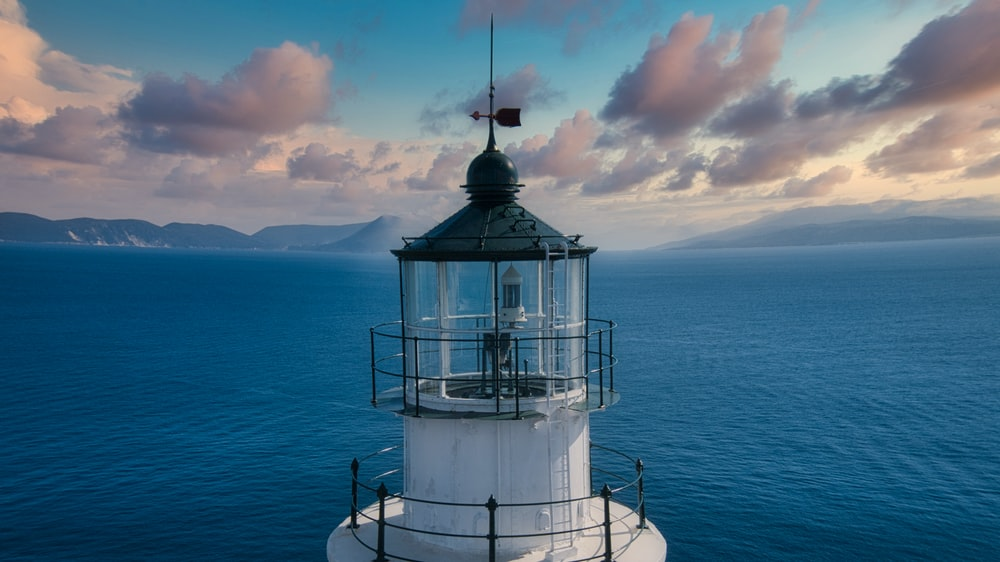white and black lighthouse on blue sea under white clouds during daytime