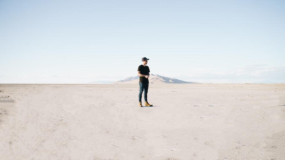 man in black jacket and blue denim jeans walking on brown sand during daytime