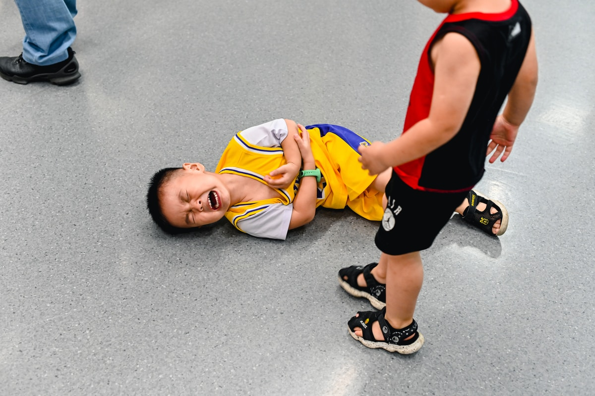 Child on the floor crying and holding their elbow.  They are wearing a yellow basketball short set.  Another child in a red an black set looms over them.