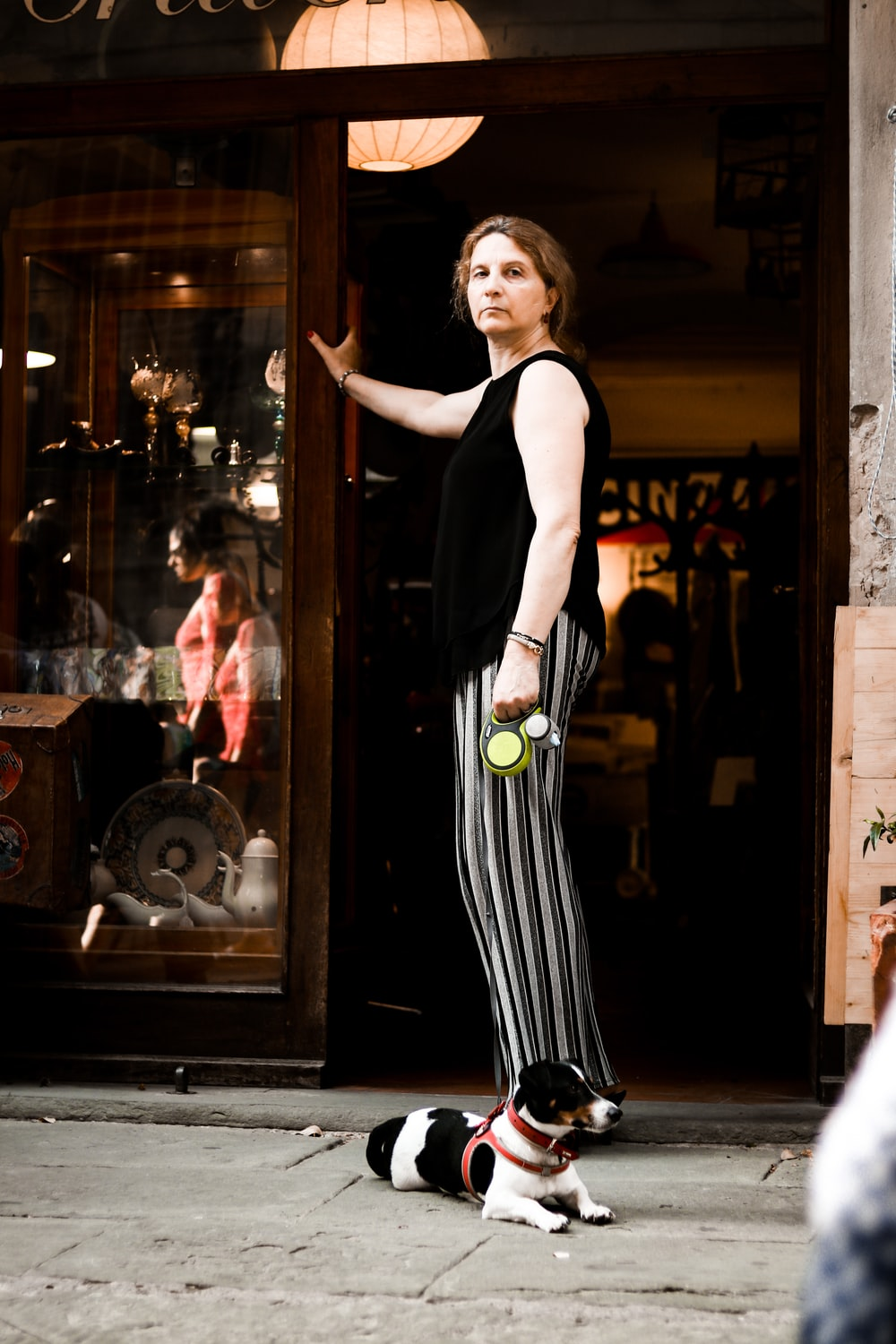 woman in black tank top and black and white striped pants standing beside glass door