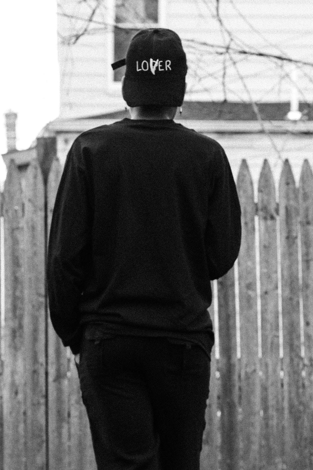 man in black long sleeve shirt and black pants standing in front of white wooden fence