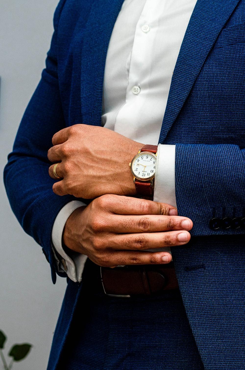 man in blue suit jacket wearing gold round analog watch