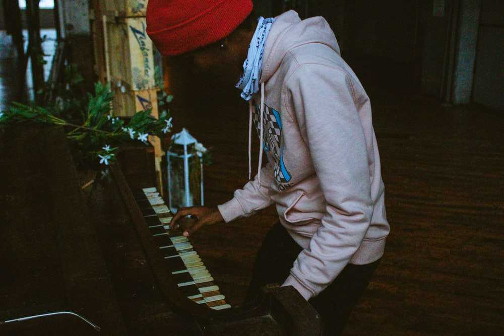 person in red knit cap and white hoodie playing piano