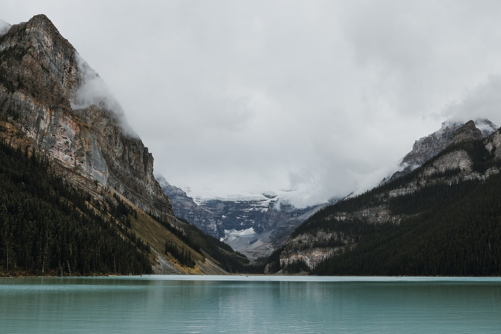 green lake near mountain under white sky during daytime