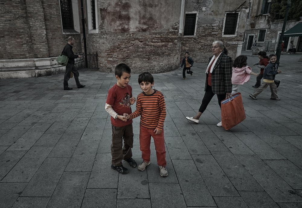 children standing on gray concrete floor during daytime