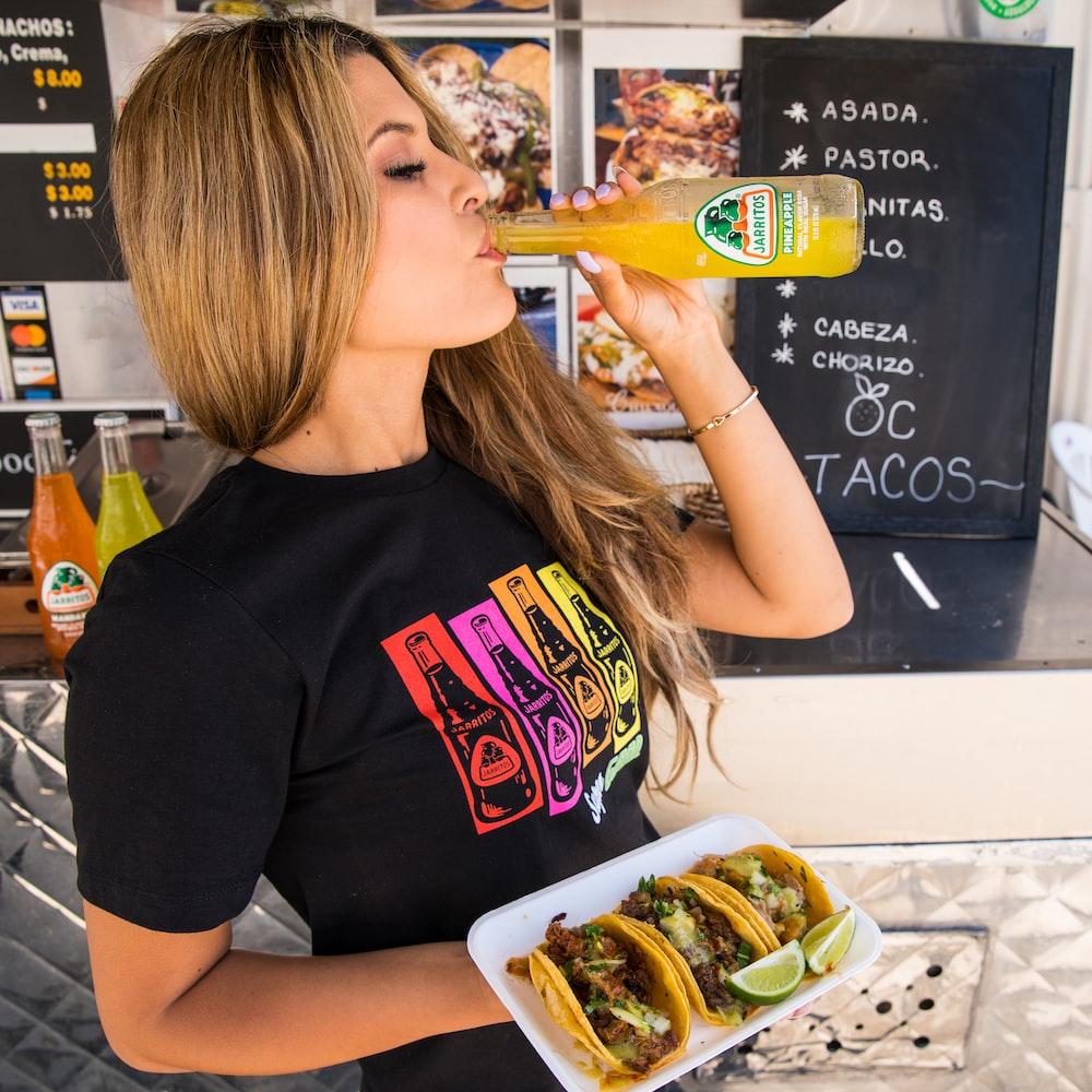 woman in black crew neck t-shirt eating burger