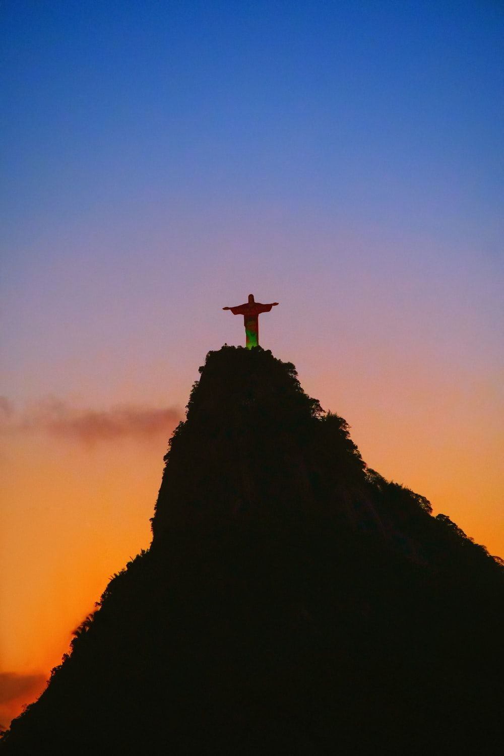 silhouette of cross on top of mountain during sunset