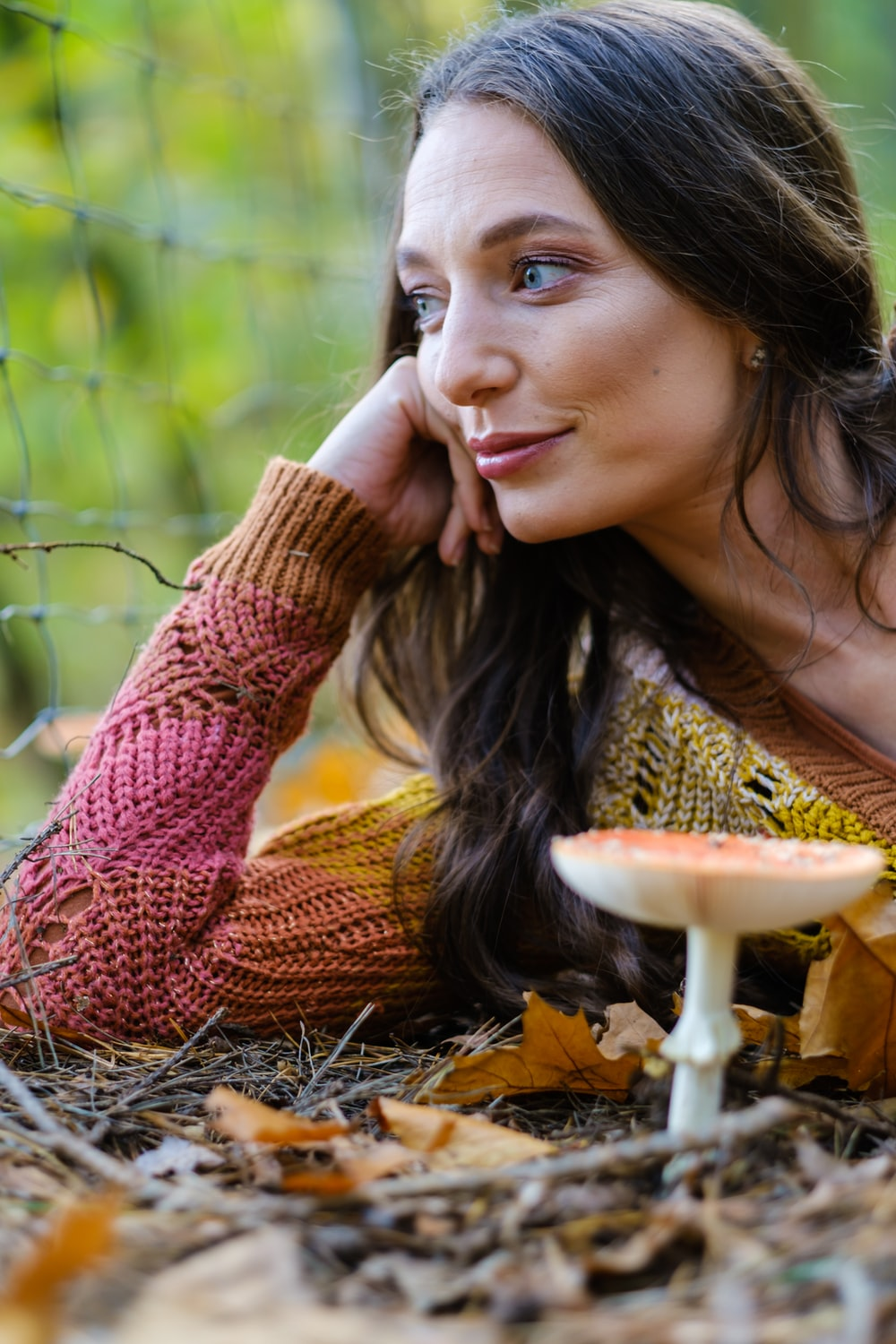 woman in brown knit sweater lying on brown dried leaves