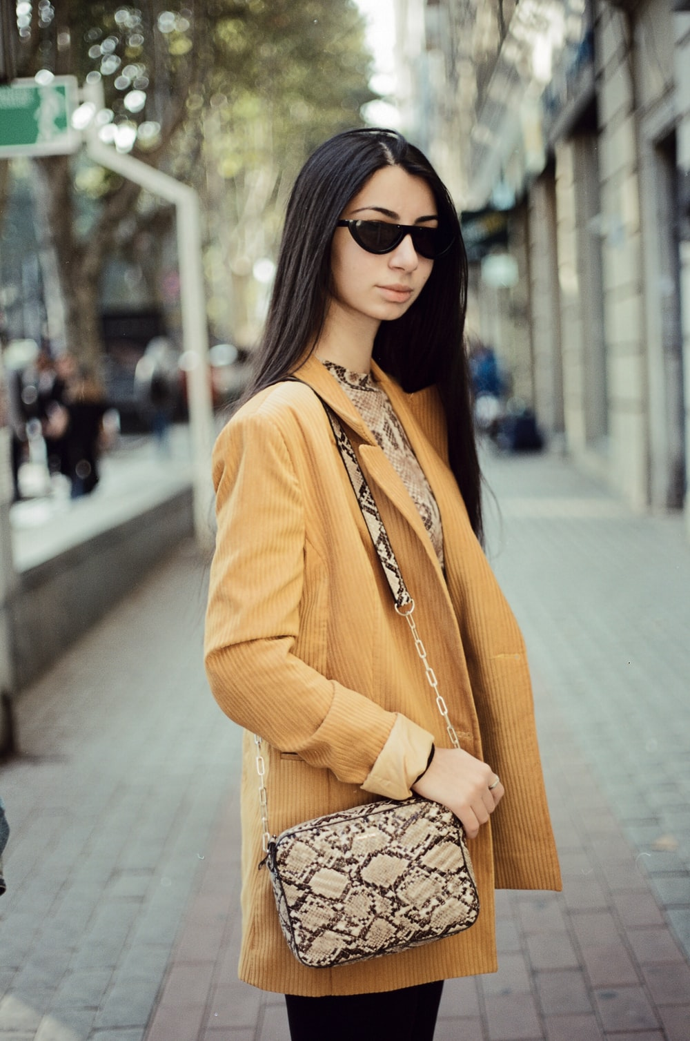 woman in orange blazer and black and white floral skirt wearing black sunglasses