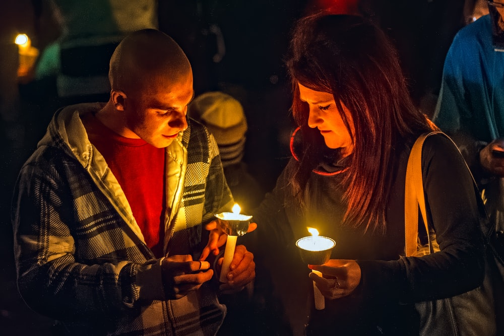 man and woman holding lighted candles