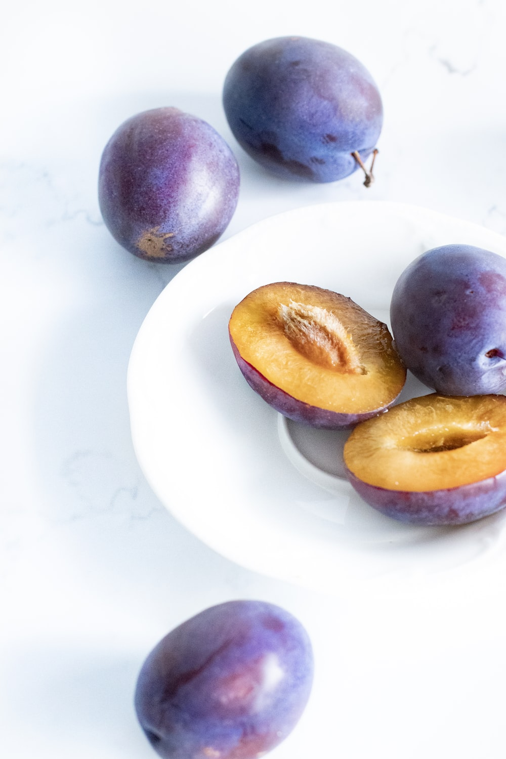 purple and yellow round fruits on white ceramic plate