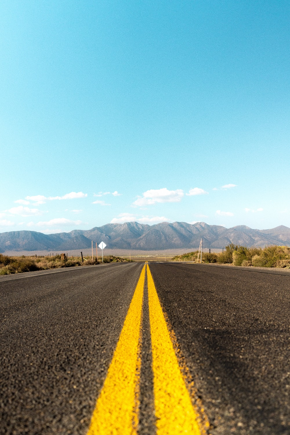 gray asphalt road near green grass field and mountains during daytime