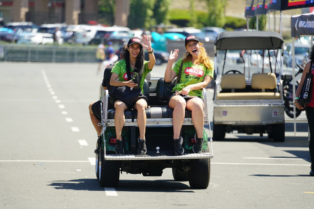 2 women in green shirt driving a car during daytime