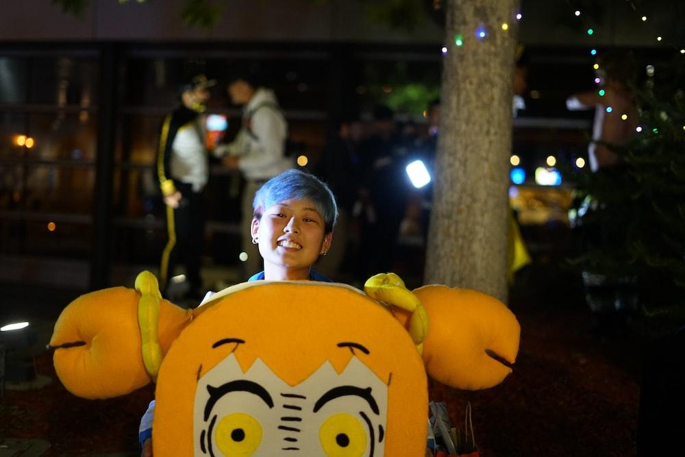 man in yellow and black batman costume standing beside yellow emoji plush toy during nighttime