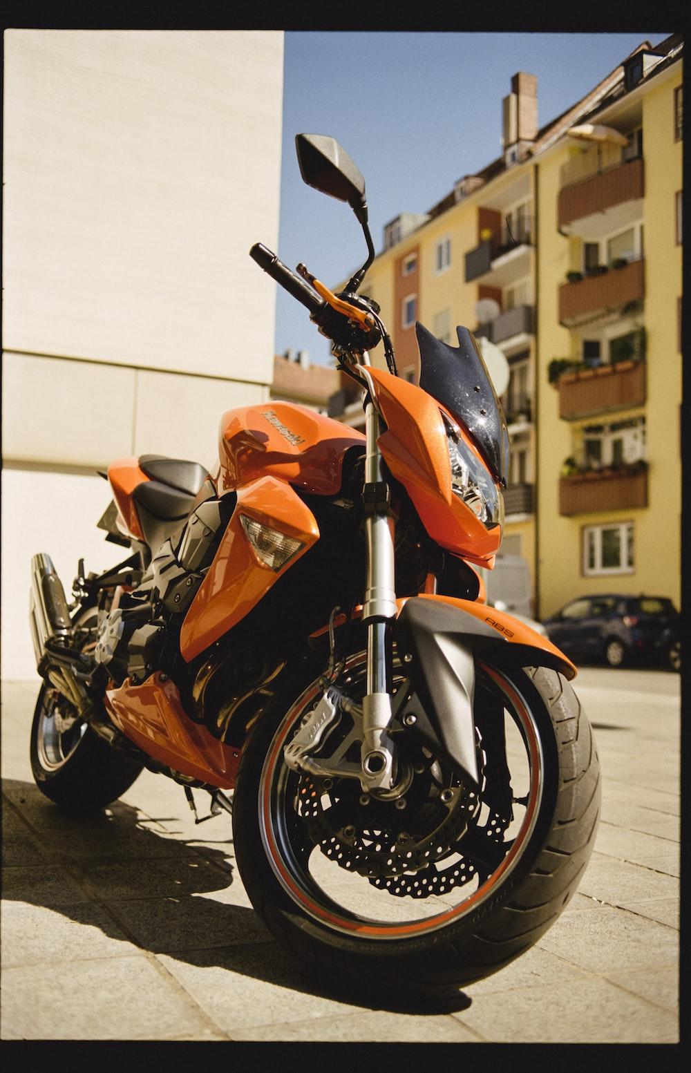 orange and black sports bike parked on sidewalk during daytime