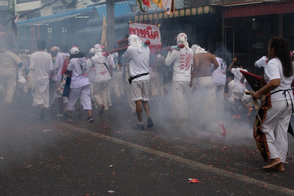 people in white uniform walking on street during daytime